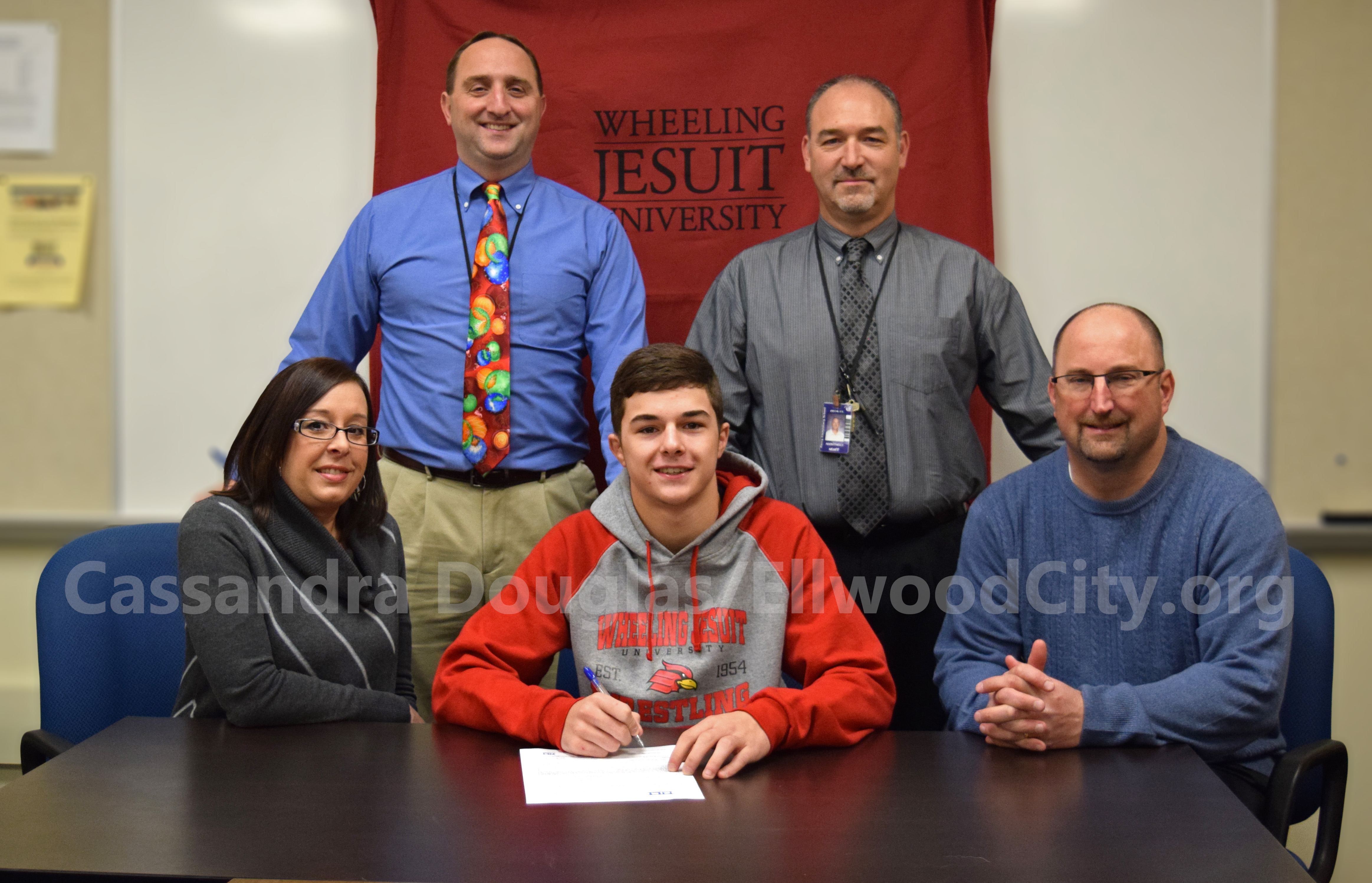 Tyler poses with his parents and school officials.